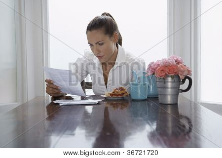 Woman going through document while having breakfast