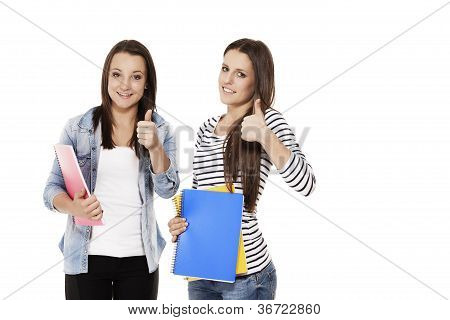 two female students showing thumbs up