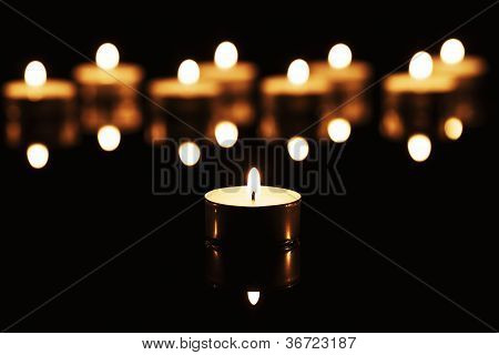 tea candle in front of many tea candles