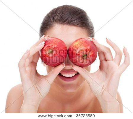 Closeup of a young smiling woman holding two apples in front of her eyes, as binoculars.