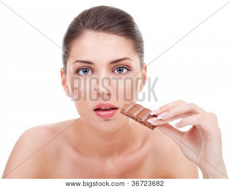 Close-up of a attractive young woman with a bitten chocolate in her hand. Young woman provoking chocolate cravings. On white background