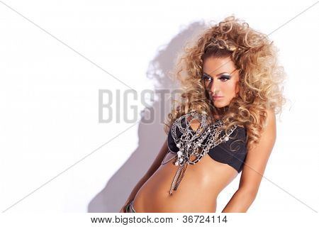 sensual young woman with lots of chains at her neck looking away from the camera