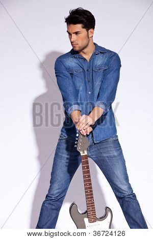 Young man in jeans shirt holding a guitar on the ground and looking to his right side on gray background