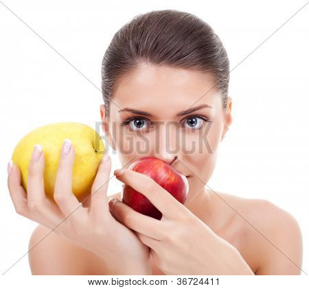 Healthy young woman holding two apples, one red and the other yellow, on white background