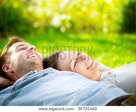 Happy Smiling Couple Relaxing on Green Grass.Park.Young Couple Lying on Grass Outdoor