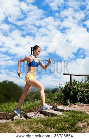 Sporty young woman running up stairs in park