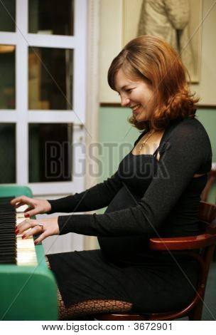 Pregnant Woman Plays On The Piano
