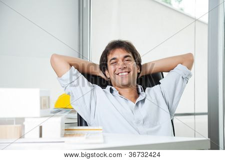Portrait of a relaxed male architect sitting in chair with hands behind head