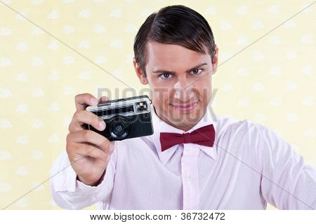Male holding retro camera in hand - shallow depth of field, focus on camera
