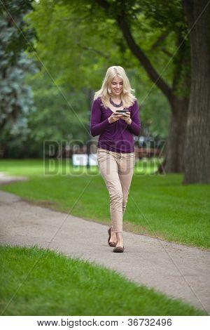 Voller Länge einer jungen Frau, die mit Smartphone, wie sie im Park geht