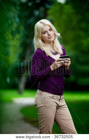 Beautiful woman in park using cell phone and looking at camera