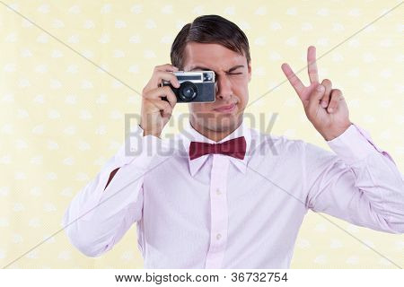 Man looking through old camera making peace sign.