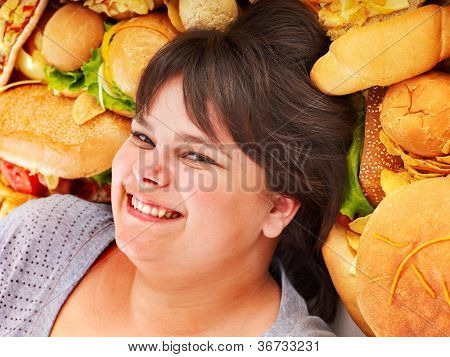 Happy overweight woman with fast food.