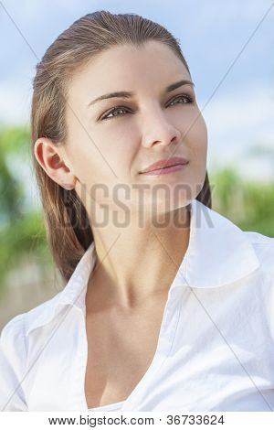 Portrait of a beautiful brunette young woman or girl with stunning green eyes, shot outside in natural light