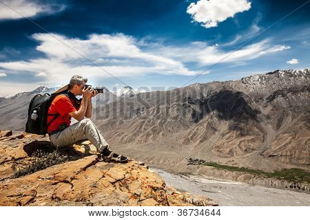 Photographer on the high mountain does its job.