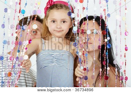 Little girl in striped sundress looks out from behind curtain of plastic beads, her parents stand behind curtain