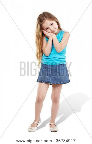 Little girl poses for camera  with one foot on the toe and with her head on folded hands