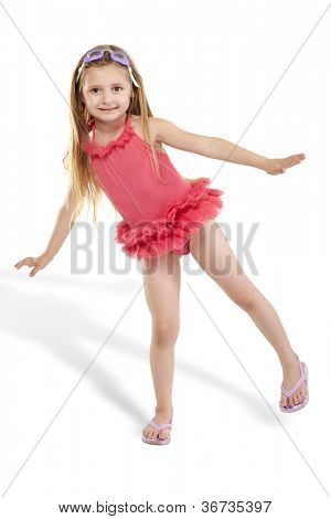 Girl in pink bathing suit with tutu poses, standing on one leg
