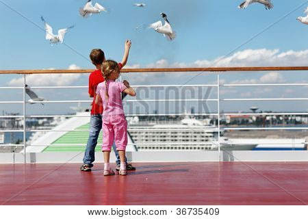 Boy in red t-shirt and his younger sister feed seaguls on deck of ship.