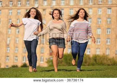 Three smiling girls run at green grass and hold hands at background of multi-storey building.