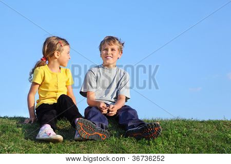 Boy and girl sit together on green grass at background of sky.