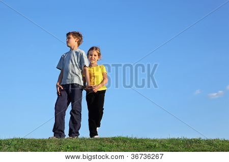 Boy and girl stand together on green grass at background of sky.