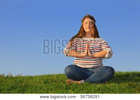 Fat girl in jeans sits at green grass and meditates at background of blue sky.