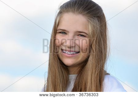 Beautiful girl with braces smiles at background of blue sky with clouds.