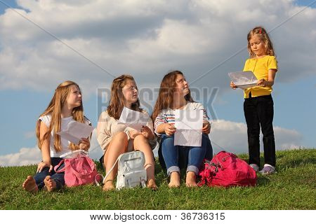 Three girls sit on grass with sheets and look at little girl standing near them and reading text at background of blue sky.