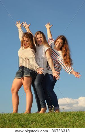 Three happy girls pose at green grass at background of blue sky.