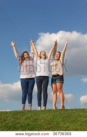Three girls hold raised their hands and scream at green grass at background of blue sky.