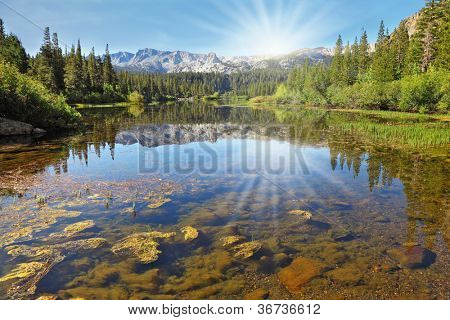 The magnificent mountains and northern sun are reflected in the smooth waters of a mountain lake