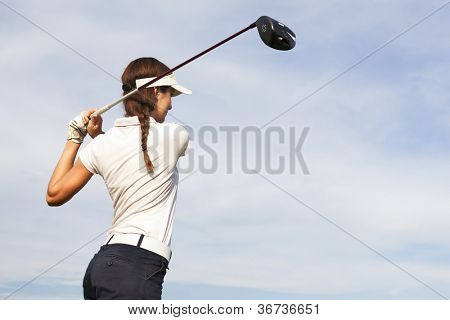 Woman golf player teeing-off with driver and beautiful sky in background, view from behind.