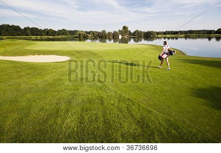 Female golf player walking  towards green on fairway carrying golf bag with clubs, lake in background.