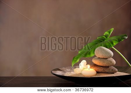 Spa still life with stacked of stone,burning candle and dishgyi leaf.
