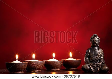 Buddha and candles on red background, religious concept.