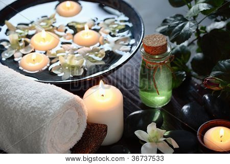 Spa still life with aromatic candles,orchid petal,oil and towel.