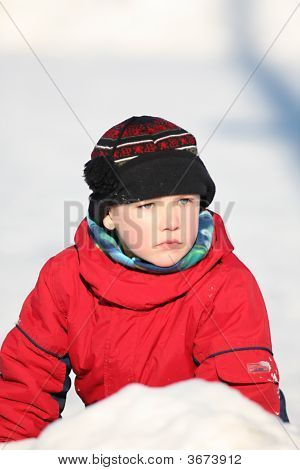 Boy In Snowsuit And Hat Sitting In A Snowbank