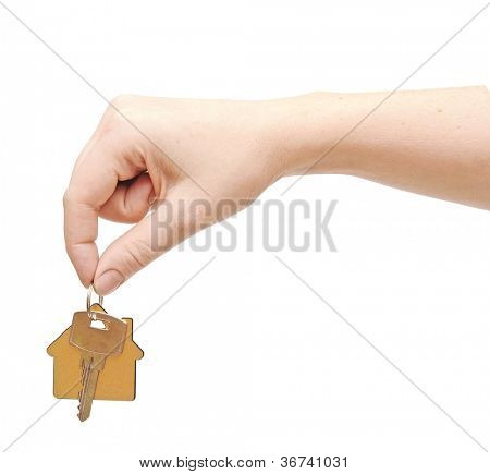 hand with chrome house key isolated on white