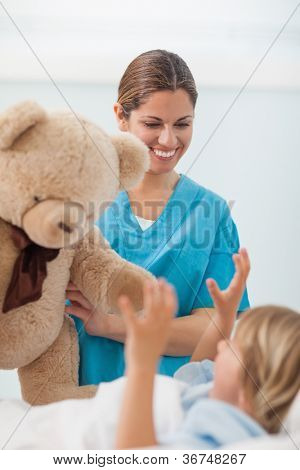 Smiling nurse showing a teddy bear to a child in hospital ward
