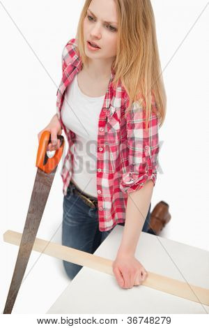 Woman using a wood saw against white background