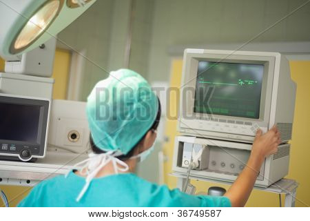 Surgeon checking a monitor in a surgical room