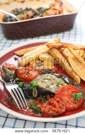 The Greek and Turkish speciality Imam Baildi, eggplant baked in olive oil with onion, tomato, garlic, parsley, topped with bread crumbs, served with potato chips or french fries