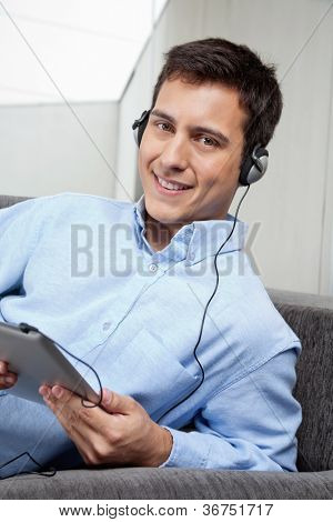 Portrait of handsome young man in formal shirt listening to music on digital tablet