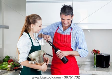 Man and woman opening wine bottle at home in kitchen.