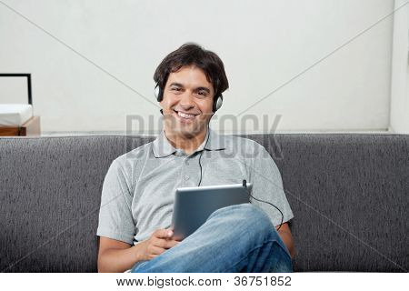 Portrait of happy young man in casual wear listening music on tablet PC