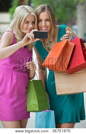 Happy young shopaholic women taking selfportrait with cellphone