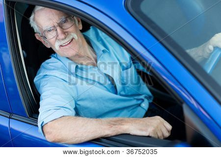 Happy elder man driving a blue car