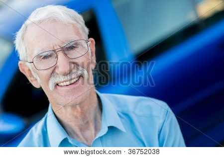 Elder man with a car looking happy and smiling