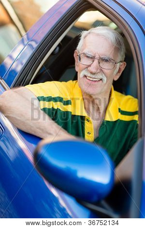 Senior man driving a car and looking happy